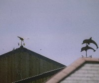 two seperate barns with two seperate weathervanes, a barn owl & a pair of leaping dolphins